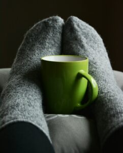 Feet in socks holding coffee mug - furnace repair
